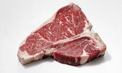 "A raw T-bone steak may leave dog owners wondering, ""Can dogs eat raw meat?"