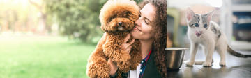 Woman holding brown fluffy puppy and kitten licking his lips