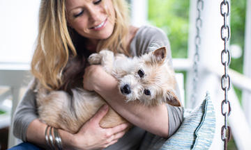 smiling blonde woman holding terrier dog on porch swing