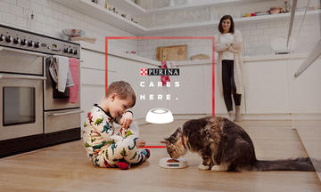 Mother and son feeding cat wholesome ingredients with purina cares promise for no artificial flavors or ingredients by 2025