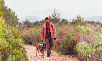 Man hiking with his dog beside him outdoors