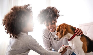young girl with curly hair smiling and petting beagle with her mom smiling at her