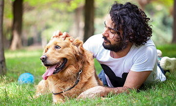Man with black hair laying in the grass with his golden retriever