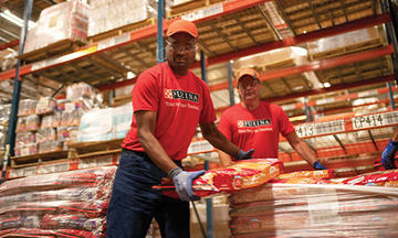 Purina employees loading pet food on a pallet for disaster assistance