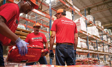 Purina employees moving dog food bags in warehouse during a disaster relief